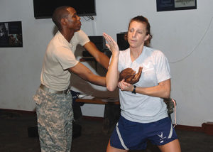 Staff Sgt. Brooke Alf, 332nd Expeditionary Aerospace Medical Squadron, demonstrates a Krav Maga defensive move to students with the assistance of Army Sgt. Rodney Moore at the Joint Base Balad Red Tail Fitness Center Nov. 5. Alf, a health services management journeyman deployed from the 59th Medical Wing at Lackland Air Force Base, Texas, volunteers to teach the self-defense class on her free time. Moore, a veterinary food inspector specialist with the 43rd Medical Detachment, assisted Alf by playing an attacker. Alf is a native of Pittsfield, Ill. (U.S. Air Force photo/Tech. Sgt. Rich Lisum)