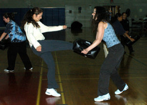 U.S. Air Force Maj. Nina Perino, with the 59th Aerospace Medical Squadron, delivers a practice kick to Lanessa Bueno a military dependent. Perino and Bueno were part of many women who took part in a Krav Maga personal defense tactics class, during the women's Sexual Assault Self-Defense Seminar, on Oct. 8, 2005, at Lackland Air Force Base, San Antonio, Texas. (U.S. Air Force photo by Mr. Alan Boedeker) (Released)